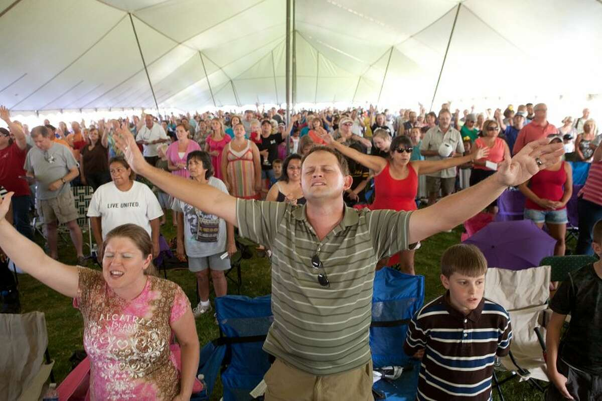 """Tanya Anderson, her husband Chance, and their son Justin, 12, join hundreds of other worshippers as they sing and pray for rain Wednesday during """"Pray for Rain Permian Basin"""" at the Rock the Desert grounds."""