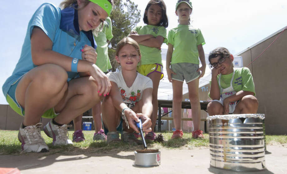 Girl Scout Charlotte Siemer learns the proper way to light a cooking burner with help from Jordi Nix (left) during summer day camp Wednesday James Durbin/Reporter-Telegram Photo: JAMES DURBIN
