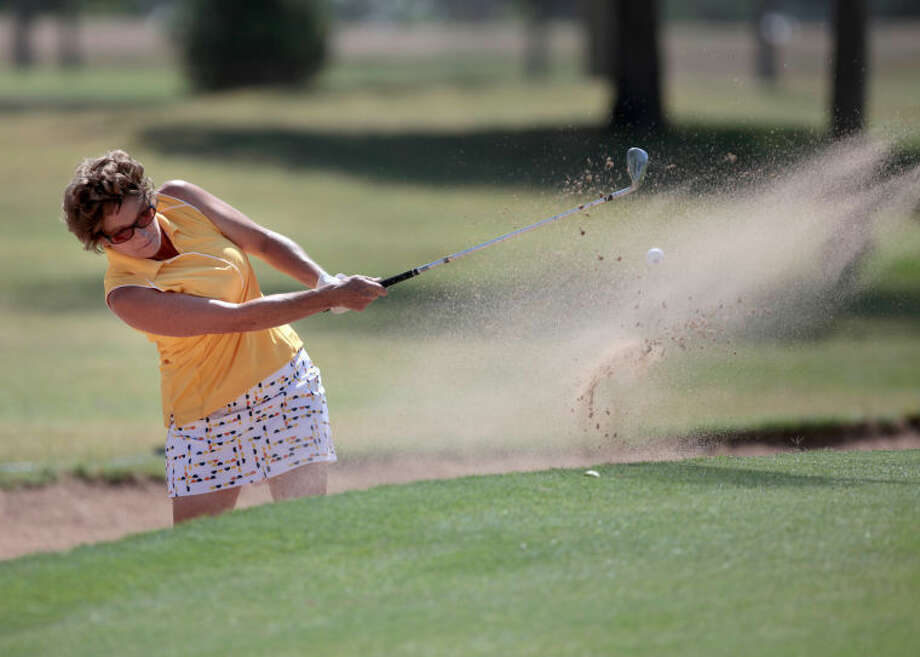 Diane Burnett punches out of the sand trap near the green on the fifth hole of the the Odessa Country Club on Tuesday during the first round of the Women's West Texas Golf Association Championship Flight. Photo: Ryan Evon|Odessa American