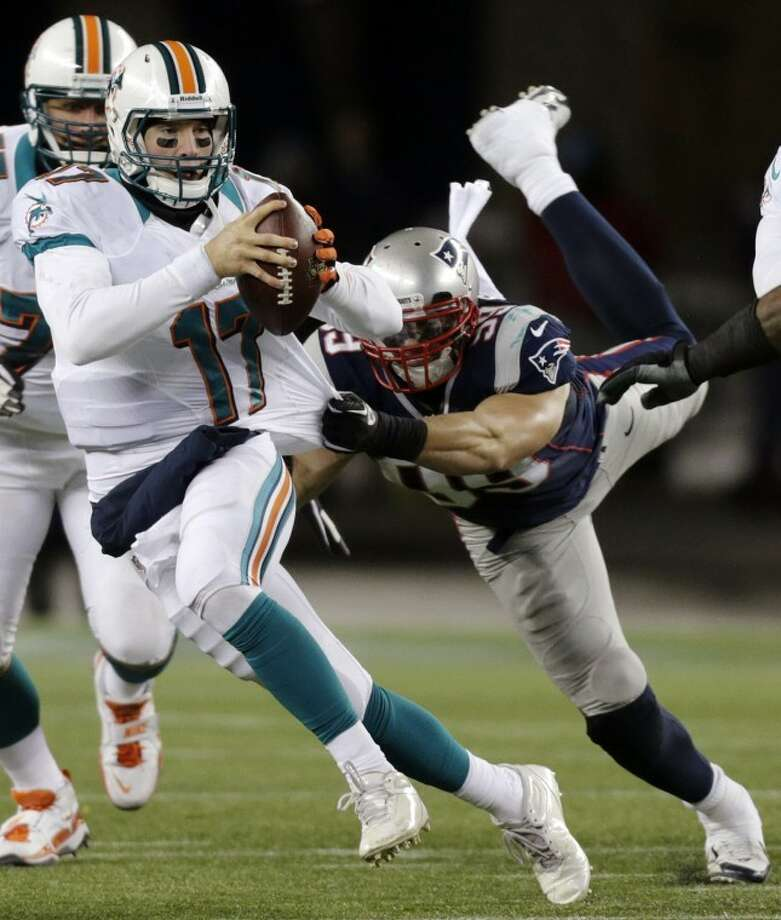 New England Patriots defensive end Trevor Scott (99) tries to tackle Miami Dolphins quarterback Ryan Tannehill (17) during the third quarter of an NFL football game in Foxborough, Mass., Sunday, Dec. 30, 2012. (AP Photo/Charles Krupa) Photo: Charles Krupa
