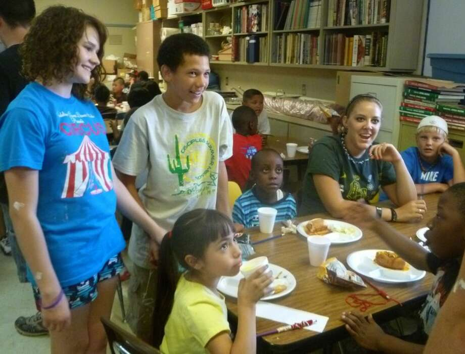 Volunteers from several churches interact with students at Casa de Amigos Thursday after serving the kids lunch. The church youth groups have been working at several nonprofits in Midland and Odessa this week as part of a trip being called �Rock the Desert and Leave a Mark.� They�ll attend Rock the Desert this weekend. Photo by Kathleen Thurber, MRT
