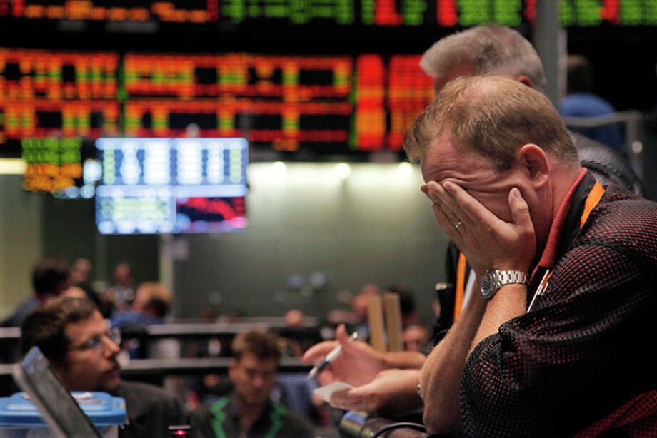 Trader Andrew Stavros reacts after the close of trading in the NASDAQ, 100 Index pit, on the floor of The CME Group Monday, Aug. 8, 2011, in Chicago. Stocks plummeted at the close after anxiety overtook investors on the first trading day since Standard & Poor's downgraded American debt. Photo: (AP Photo/M. Spencer Green) / AP