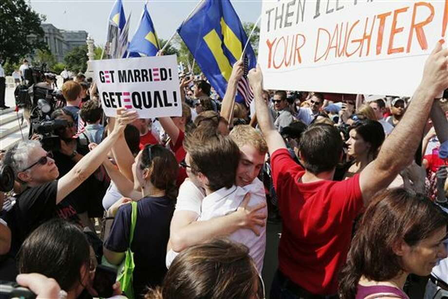 Supporters of gay marriage embrace outside the U.S. Supreme Court in Washington, Wednesday, June 26, 2013, after the court cleared the way for same-sex marriage in California by holding that defenders of California's gay marriage ban did not have the right to appeal lower court rulings striking down the ban. (AP Photo/Charles Dharapak) Photo: Charles Dharapak / AP