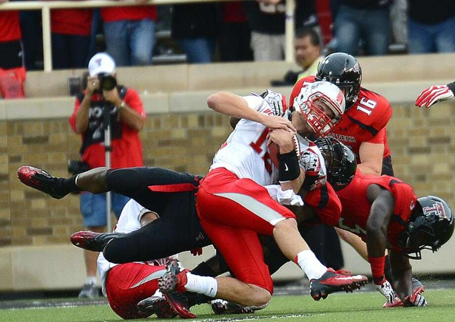 New Mexico quarterback B R Holbrook (12) is taken down by a host of Red Raider defenders in Saturday night action in Lubbock at Jones AT&T Stadium. Photo: Wade H Clay