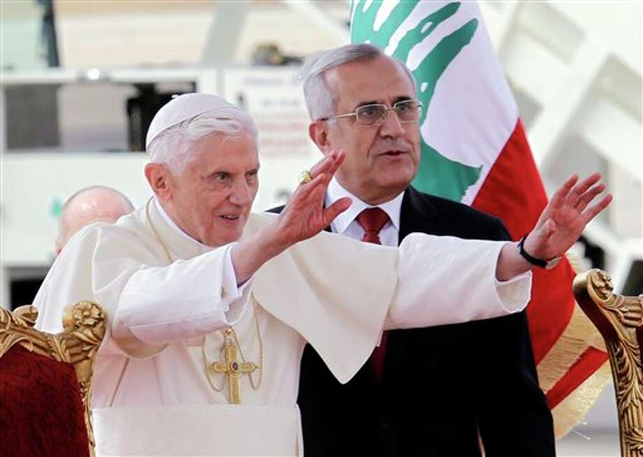 "Pope Benedict XVI stands next to Lebanese President Michel Suleiman as he waves to the crowd at Rafik Hariri international airport, in Beirut, Lebanon, Friday, Sept. 14, 2012. Pope Benedict XVI arrived in Lebanon on Friday to urge peace at a time of great turmoil in the Middle East, saying the import of weapons to Syria during the country's civil war is a ""grave sin."" The three-day visit comes at a time of turmoil in the region — the civil war in neighboring Syria and in the aftermath of a mob attack that killed several Americans in Libya, including the U.S. ambassador. (AP Photo/Bilal Hussein) Photo: Bilal Hussein / AP"