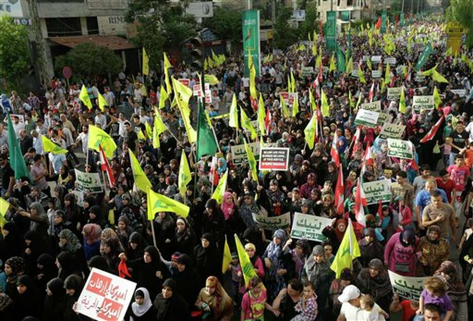 "Hezbollah supporters wave their flag and hold up Arabic banners that read, ""At your service God's prophet, America equals terrorism, and America does not equal freedom,"" during a rally denouncing an anti-Islam film that has provoked a week of unrest in Muslim countries worldwide, in the southern suburb of Beirut, Lebanon, Monday Sept. 17, 2012. Hezbollah's leader Hassan Nasrallah, nor shown, who does not usually appear in public for fear of assassination, called for Monday's protests in Beirut, saying the U.S. must be held accountable for the film because it was produced in America. (AP Photo/Hussein Malla) Photo: Hussein Malla / AP"