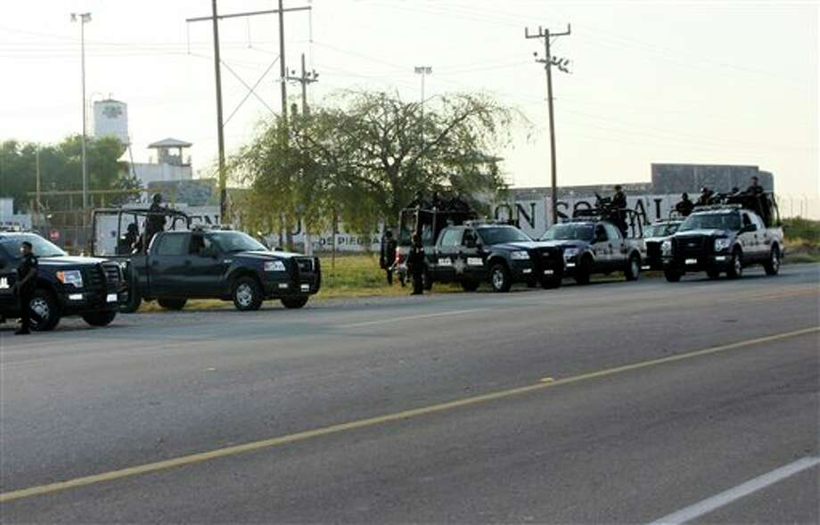A group of Mexican federal police stand in front of the prison in Piedras Negras, Mexico, Monday Sept. 17, 2012. Authorities say 132 inmates have escaped from this jail in northern Mexico, sparking a search by federal police and soldiers in an area close to the U.S. border. (AP Photo/Adriana Alvarado) Photo: Adriana Alvarado / AP2012