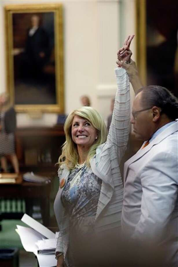 Sen. Wendy Davis, D-Fort Worth, left, who tries to filibuster an abortion bill, reacts as time expires, Wednesday, June 26, 2013, in Austin, Texas. Amid the deafening roar of abortion rights supporters, Texas Republicans huddled around the Senate podium to pass new abortion restrictions, but whether the vote was cast before or after midnight is in dispute. If signed into law, the measures would close almost every abortion clinic in Texas. (AP Photo/Eric Gay) Photo: Eric Gay / AP
