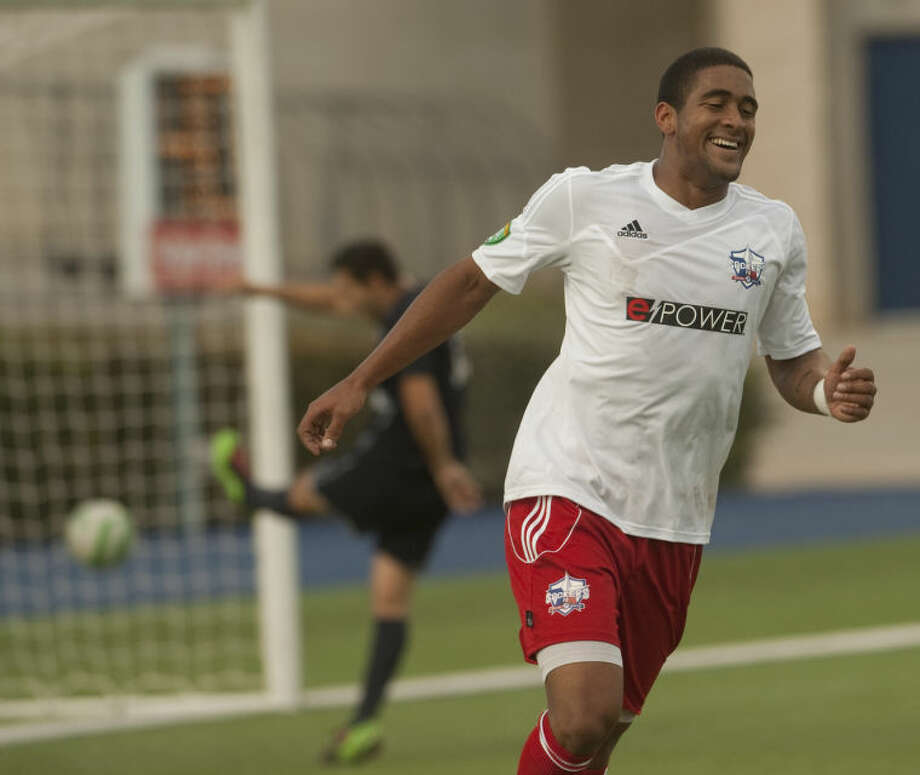 Sockers Len Smith smiles after scoring the first goal as a Patriots players kicks the ball in frustration Saturday at Grande Communication Stadium. Tim Fischer\Reporter-Telegram Photo: Tim Fischer