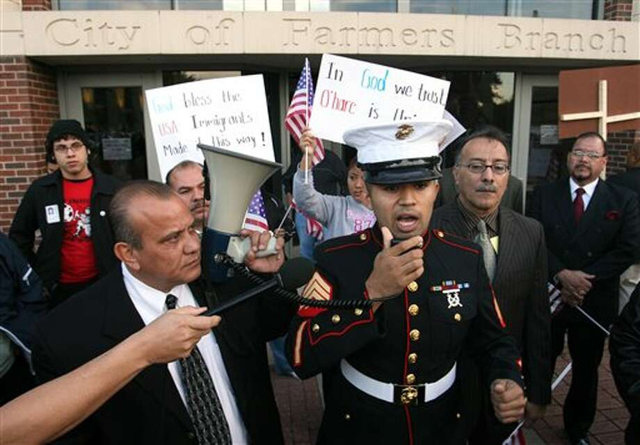 FILE - In this Nov. 13, 2006 file photo, former Marine Sgt. Salvadaor Parada, right, speaks to protesters during a rally outside city hall in Farmers Branch, Texas. A federal appeals court will review Farmers Branch's ordinance, which allows the city building inspector to evict any illegal immigrant renters. (AP Photo/Rex C. Curry, File) Photo: REX C. CURRY / AP