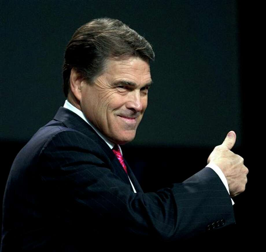 FILE - In this Aug. 6, 2011, file photo Texas Gov. Rick Perry gives a thumbs up as he takes the stage at The Response, a call to prayer for a nation in crisis in Houston. The GOP electorate has made clear in polls that it wants more choices, perhaps a conservative who is strong both on economic and social issues, leading Perry to consider a White House bid. A nationally televised debate, a test vote in Iowa and a candidacy by Perry, should he decide to seek the GOP nomination, could shake up the Republican presidential race in the coming days. (AP Photo/David J. Phillip, File) Photo: David J. Phillip / AP2011