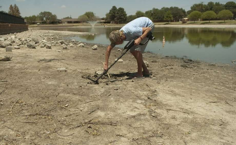 FILE - Tom Byrom uses a metal detector he found at his parents Aug. 10 to search for lost treasures along the dried up banks of Wadley Barron Pond. Photo by Tim Fischer/Midland Reporter-Telegram Photo: Tim Fischer