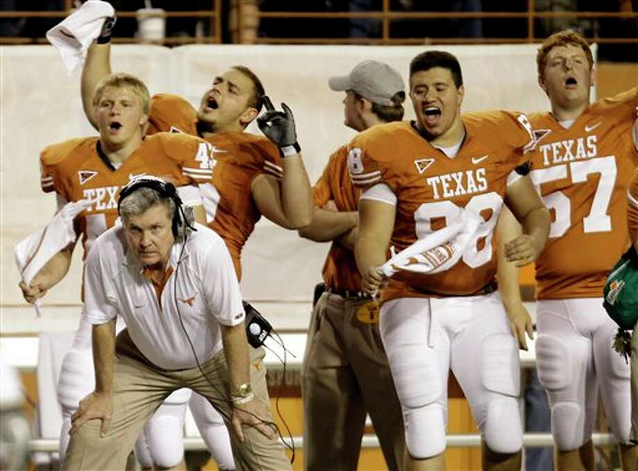 FILE- In this Nov. 20, 2010 file hoto, Texas coach Mack Brown, left front, keeps watch on the team's game against Florida Atlantic during the fourth quarter of an NCAA college football game in Austin, Texas. (AP Photo/Eric Gay) Photo: Eric Gay / AP2010