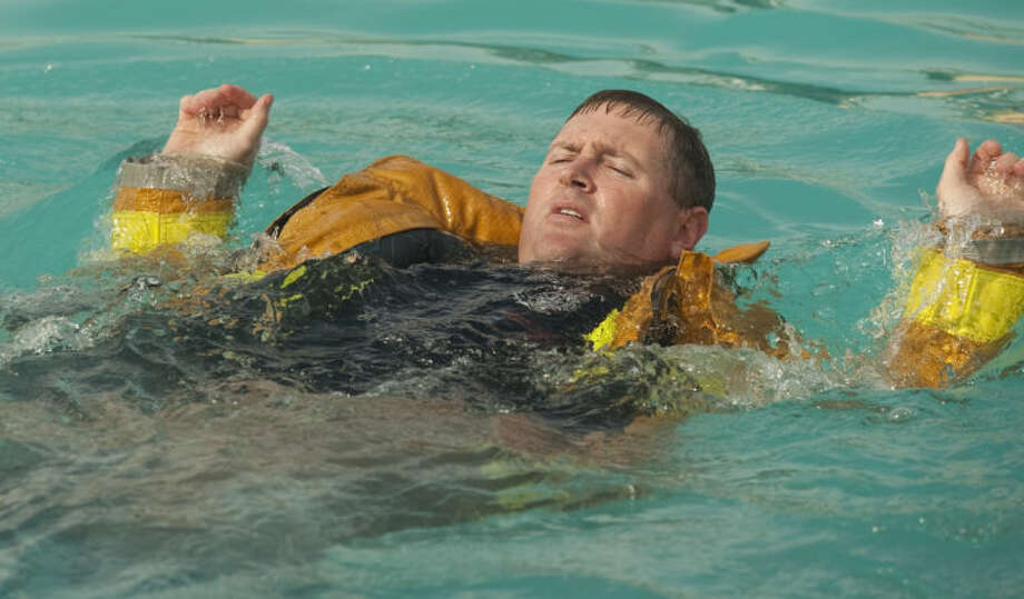 Midland firefighterTim Harris treads water and swims in full bunker gear in the deep end of Washington Pool as he and others practice water safety training. Tim Fischer\Reporter-Telegram Photo: Tim Fischer