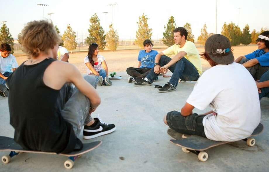 """A group of around 30 skateboarders gathers around """"Real Talk"""" group leader Bo Celenze to talk about issues affecting their lives and how Jesus can help them through it recently at Beal Park. Cindeka Nealy/Reporter-Telegram Photo: Cindeka Nealy"""