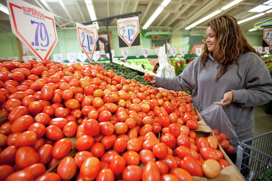 FILE - In this May 23, 2011 file photo, consumer Sonia Romero shops for tomatoes at a Superior Grocers store in Los Angeles. As food costs continue rising, many grocery shoppers are seeking new ways to cut costs. After you've tried every store brand and linked, scanned and clipped every coupon in sight, what about buying in bulk? (AP Photo/Damian Dovarganes, File) Photo: Damian Dovarganes / AP2011