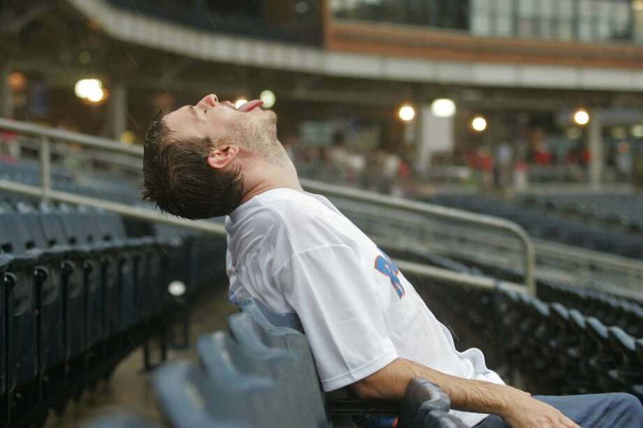 Kevin Leoffler is one of only a handful of fans who stayed in their seats to enjoy the rain Thursday at Citibank Ballpark. The RockHounds will play the Tulsa Drillers in a doubleheader today to make up Thursday night's game that was canceled because the weather. Photo: Cindeka Nealy/Reporter-Telergam