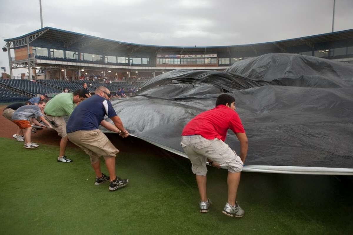 Members of the RockHounds staff battle the wind as they try to lay a tarp over the infield to protect it from the rain Thursday at Citibank Ballpark. The RockHounds will play the Tulsa Drillers in a doubleheader today to make up Thursday's game that was canceled because of the weather.