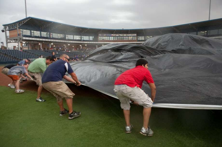 Members of the RockHounds staff battle the wind as they try to lay a tarp over the infield to protect it from the rain Thursday at Citibank Ballpark. The RockHounds will play the Tulsa Drillers in a doubleheader today to make up Thursday's game that was canceled because of the weather. Photo: Cindeka Nealy/Reporter-Telegram