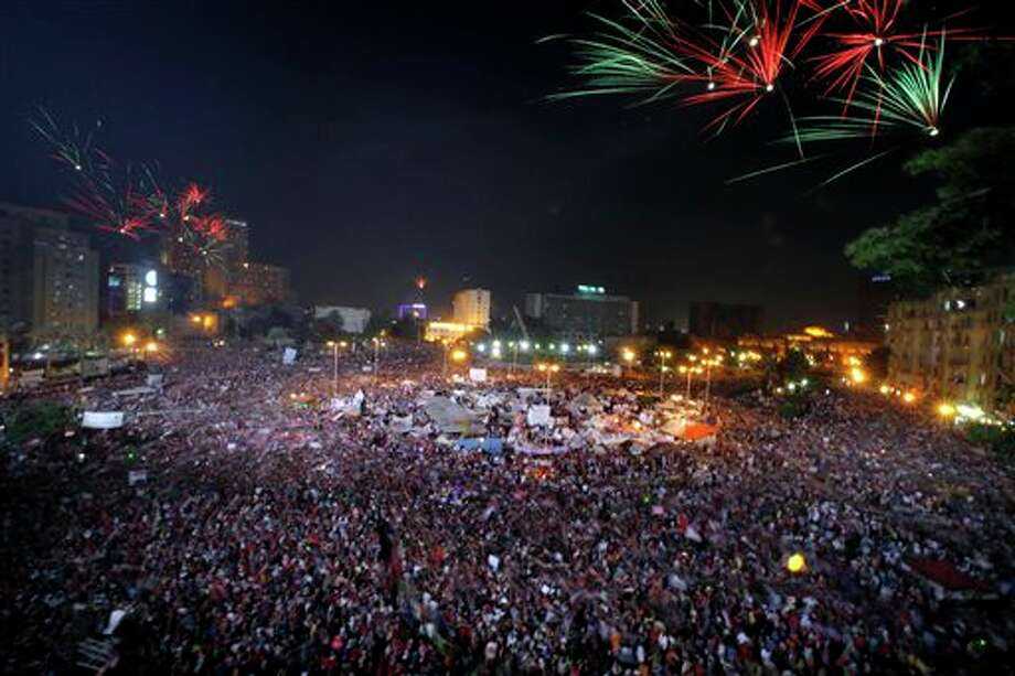 Fireworks light the sky as opponents of Egypt's Islamist President Mohammed Morsi celebrate in Tahrir Square in Cairo, Egypt, Wednesday, July 3, 2013. Army troops backed by armor and including commandos have deployed across much of the Egyptian capital, near protest sites and at key facilities and major intersections. The deployment is part of a bid by the military to tighten its control of key institutions Wednesday, slapping a travel ban on embattled president Mohammed Morsi and top allies in preparation for an almost certain push to remove the Islamist president with the expiration of an afternoon deadline. (AP Photo/Amr Nabil) Photo: Amr Nabil / AP