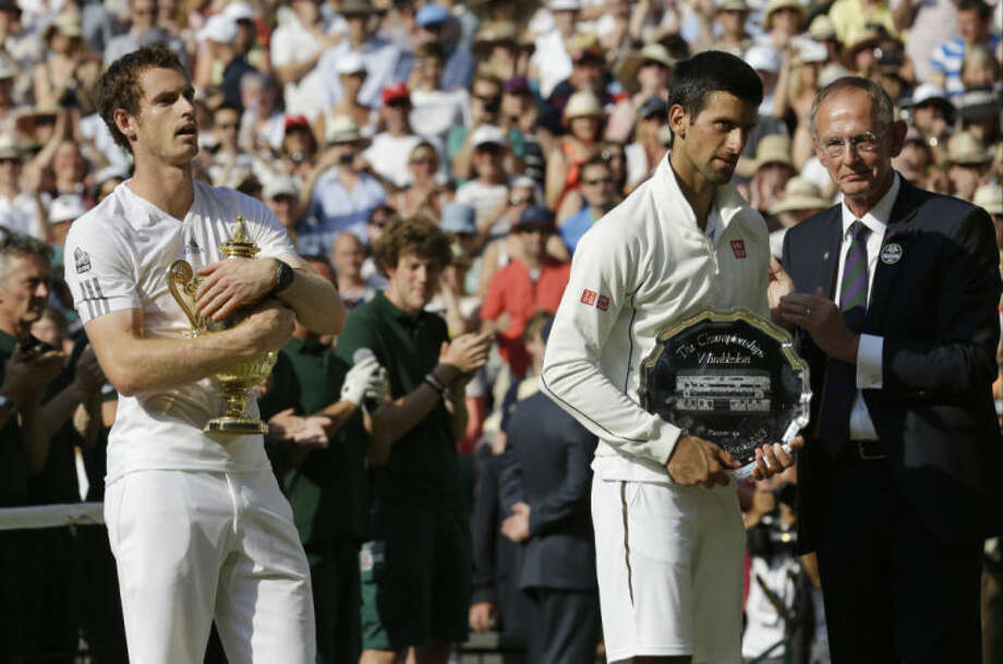 Andy Murray of Britain, left, holds his trophy after he won against Novak Djokovic of Serbia, second from right, following the Men's singles final match at the All England Lawn Tennis Championships in Wimbledon, London, Sunday, July 7, 2013. (AP Photo/Anja Niedringhaus, Pool) Photo: Anja Niedringhaus