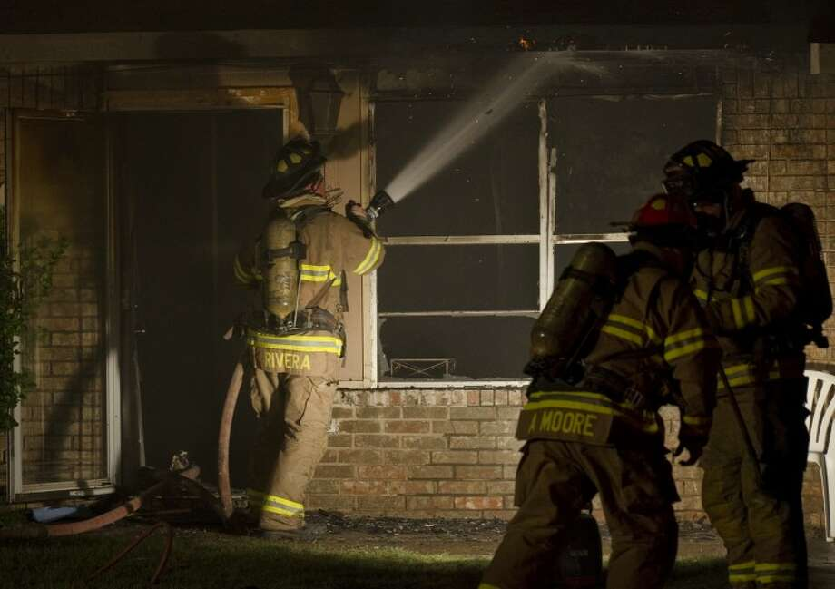 Midland firefighters battle a blaze at a residence in the 1600 block of E. Pine Sunday night. No one was injured in the single family home, but the living room was destroyed and the entire home suffered heavy smoke damage. Tim Fischer/Reporter-Telegram Photo: Tim Fischer