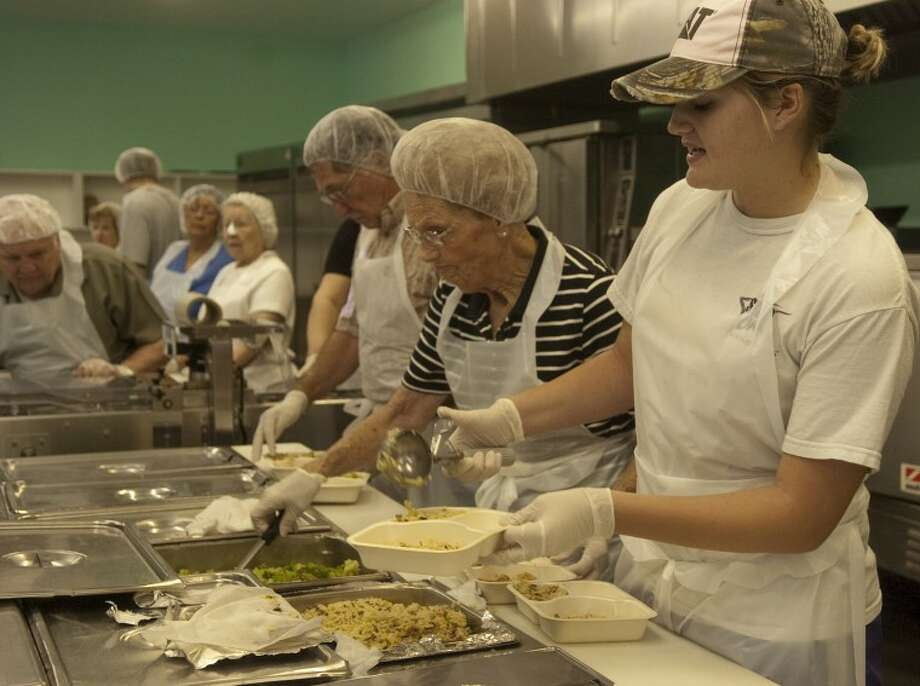 Lindsay Leible fills plates in the Meals on Wheels kitchen as she and other volunteers help put the hot meals together Monday morning. Photo by Tim Fischer/Midland Reporter-Telegram Photo: Tim Fischer