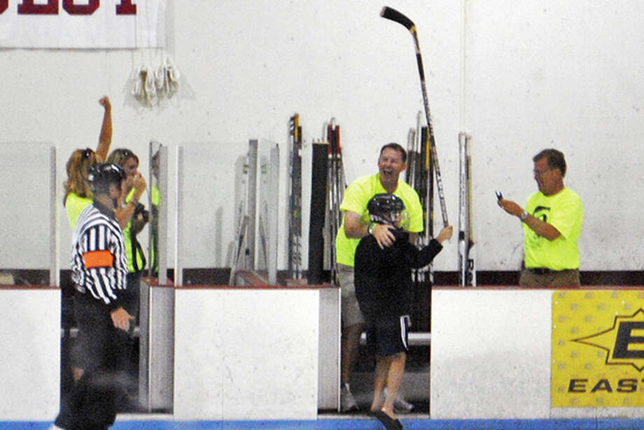 Nate Smith, 11, holds his stick up in jubilation after sinking a trick shot during a charity hockey game Thursday, Aug. 11, 2011, in Faribault, Minn. Nate shot a puck 89 feet and through a tiny hole barely larger than the puck to win a $50,000 prize, but may be whistled for a rules violation because it was his brother Nick's name that had been drawn for the chance to make the shot. Nate's father Pat Smith wanted to set a good example for the kids and told organizers the next day. The promotions company that insured the raffle, Odds On Promotions of Reno, Nev., haven't said yet if it will pay. (AP Photo/Daily News, Brendan Burnett-Kurie) Photo: Brendan Burnett-Kurie / Daily News