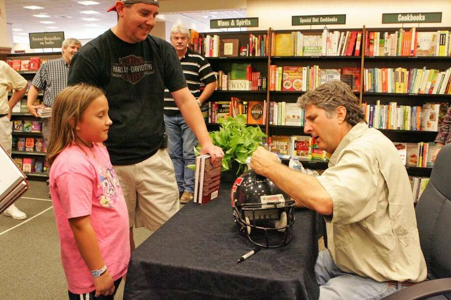 "Joe Bishop and his daughter Hannah, 8, watch as former Texas Tech coach Mike Leach sings his name to a helmet after autographing two of his ""Swing Your Sword"" books Tuesday during a book signing at Barnes and Nobles. Cindeka Nealy/Reporter-Telegram Photo: Cindeka Nealy"