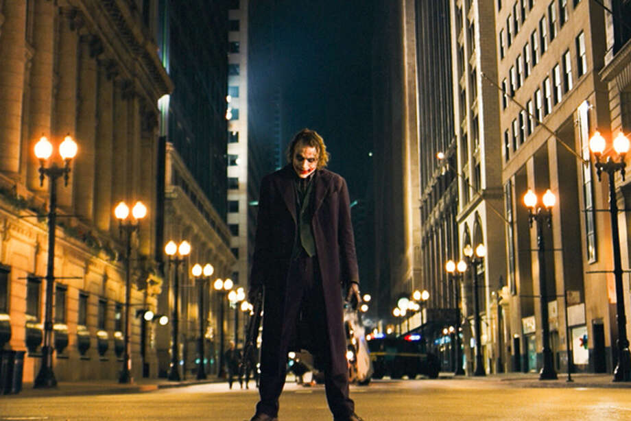 """FILE - In this undated image released by Warner Bros., Heath Ledger is shown in a scene from, """"The Dark Knight."""" in the decade since Sept. 11, movies have turned dark, paranoid and questioning. Even in the most popular films of the decade, a post-9/11 atmosphere is unmistakable. (AP Photo/Warner Bros.) Photo: Anonymous / AP2008"""