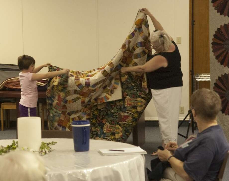 Cathie Tinney and her granddaughter Edith Tinney show off a quilt Cathie recently finished during a Midland Quilters Guild meeting. Photo by Tim Fischer/Midland Reporter-Telegram Photo: Tim Fischer