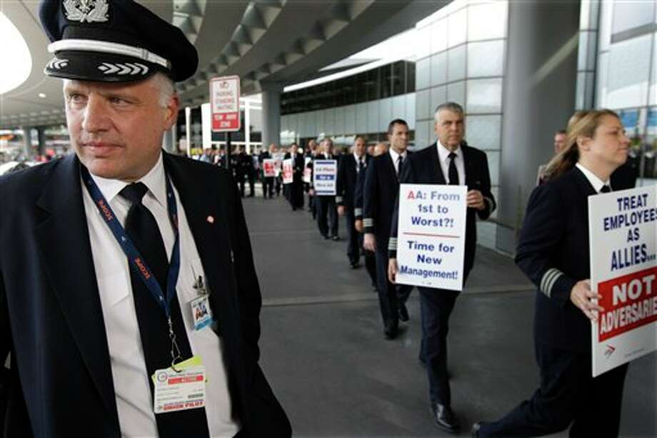 """FILE- In this Thursday, Sept. 20, 2012, file photo, Captain Mike McClellan, ORD Domicile Chairman of the Allied Pilots Association left, joins over 200 American Airline pilots marching on a picket line at O'Hare International Airport, in Chicago. American Airlines said Thursday, Sept. 27, 2012, if pilots don't end actions that are disrupting its flights, it will take their union to court. A top American Airlines executive told union leaders that some pilots were conducting """"an unlawful, concerted effort to damage the company"""" by filing more maintenance complaints and other tactics, leading to a surge in late and canceled flights.(AP Photo/M. Spencer Green, File) Photo: M. Spencer Green / AP"""