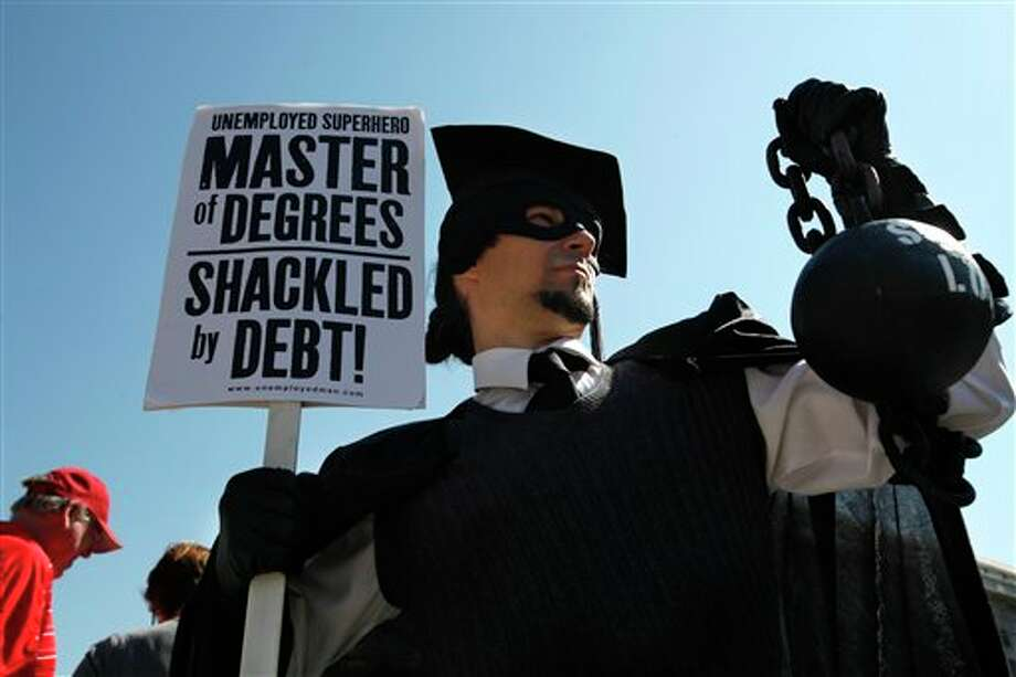 "FILE- In this Oct. 6, 2011, file photo, Gan Golan, of Los Angeles, dressed as the ""Master of Degrees,"" holds a ball and chain representing his college loan debt, during Occupy DC activities in Washington. With college enrollment growing, student debt has stretched to a record number of U.S. households — nearly 1 in 5 — with the biggest burdens falling on the young and poor, according to a study based on the Survey of Consumer Finances released Wednesday, Sept. 26, 2012. (AP Photo/Jacquelyn Martin, File) Photo: Jacquelyn Martin / AP"