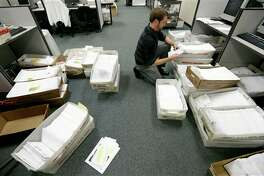 Election clerk Karl Althaus sorts through boxes of absentee ballots at the Polk County Election Office, Wednesday, Sept. 26, 2012, in Des Moines, Iowa. Voting in Iowa, one of 32 states that allow early voting, begins Thursday morning. (AP Photo/Charlie Neibergall)