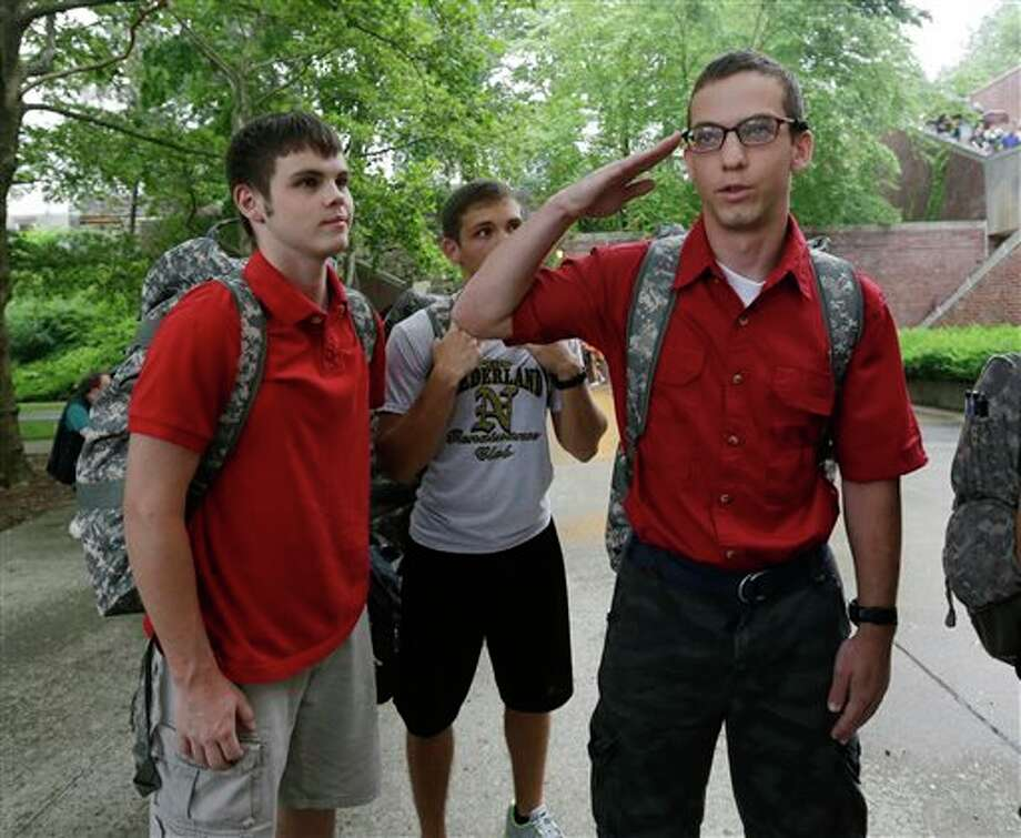 Cadet candidate Noah Ogrydziak, right, salutes an officer as he and his brothers Cole, left, and his twin Sumner, 18, wait to be processed during Reception Day at the U.S. Military Academy at West Point on Monday, July 1, 2013, in West Point, N.Y. (AP Photo/Mike Groll) Photo: Mike Groll / AP