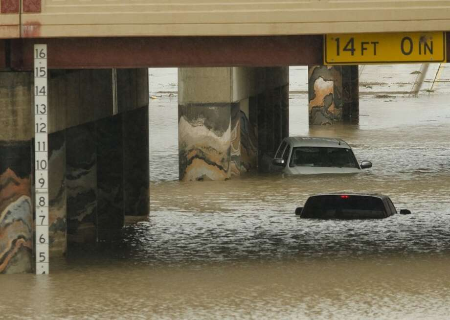 Two pickup trucks sit flooded and abandoned on Big Spring Street under the RR underpass Friday morning. Tim Fischer\Reporter-Telegram Photo: Tim Fischer