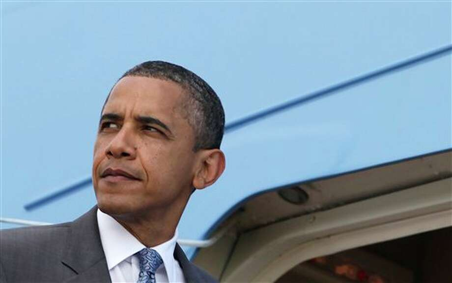 President Barack Obama boards Air Force One at Andrews Air Force Base, Md.,Thursday, Aug. 18, 2011, en route to Martha's Vineyard for a family vacation. (AP Photo/Carolyn Kaster) Photo: Carolyn Kaster / AP