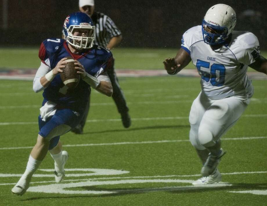 Midland Christian's Mason McClendon rolls out as he is chased by Southwest Christian's Jeremy Carroll Friday night at Mustang Field. Tim Fischer\Reporter-Telegram Photo: Tim Fischer