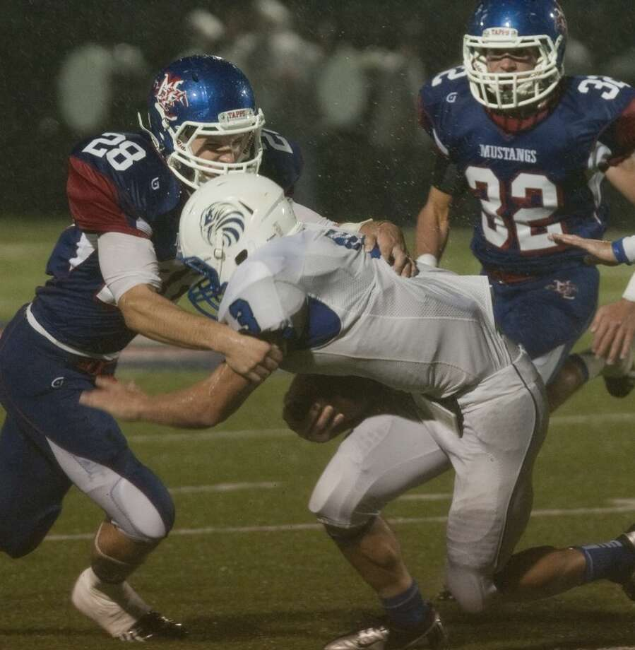 Midland Christian's Jarrod Koym wraps up Southwest Christian's Ayden Broadwater Friday night at Mustang Field. Tim Fischer\Reporter-Telegram Photo: Tim Fischer