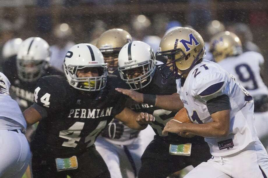 Midland High's Lance White (21) runs as Permian's Junior Gomez (44) and Matt Berzoza (46) tackle him during the game Friday at Ratliff Stadium. Photo: Albert Cesare