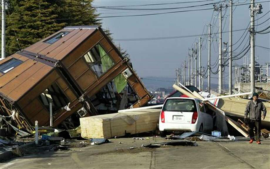 This March 12, 2011 file photo a man walks by a collapsed house and debris at Sendai Port in Sendai, northeastern Japan, following Friday's 8.9-magnitude quake. New research appearing Thursday July 11, 2013 in the journal Science suggests that such powerful distant quakes can trigger minor shaking around wastewater injection sites in the U.S. Midwest. (AP Photo/Koji Sasahara,File) Photo: Koji Sasahara / AP