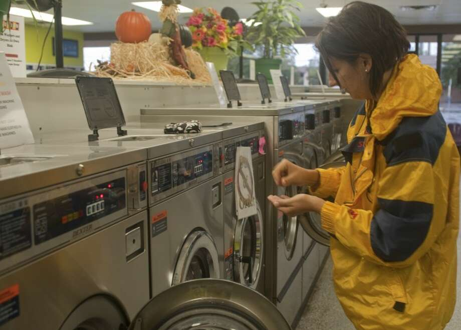 Vanessa Claybrooke puts quarters in a washing machine Friday at Wash 'Em Up laundromat as she and others wash and dry their clothes. Tim Fischer\Reporter-Telegram Photo: Tim Fischer