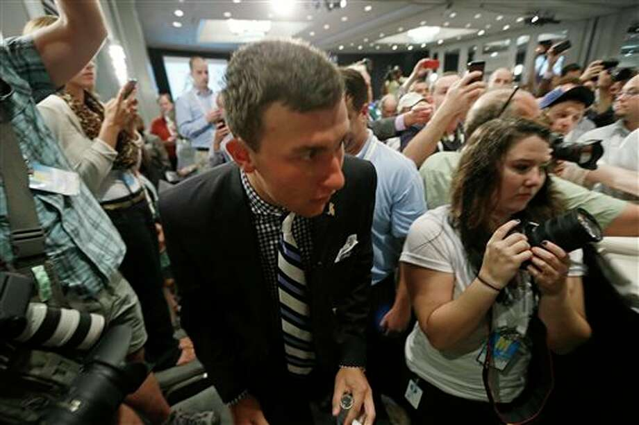 Texas A&M quarterback Johnny Manziel fights his way through a crowd of photographers and reporters as he arrives for the Southeastern Conference football Media Days in Hoover, Ala., Wednesday, July 17, 2013. (AP Photo/Dave Martin) Photo: Dave Martin / AP
