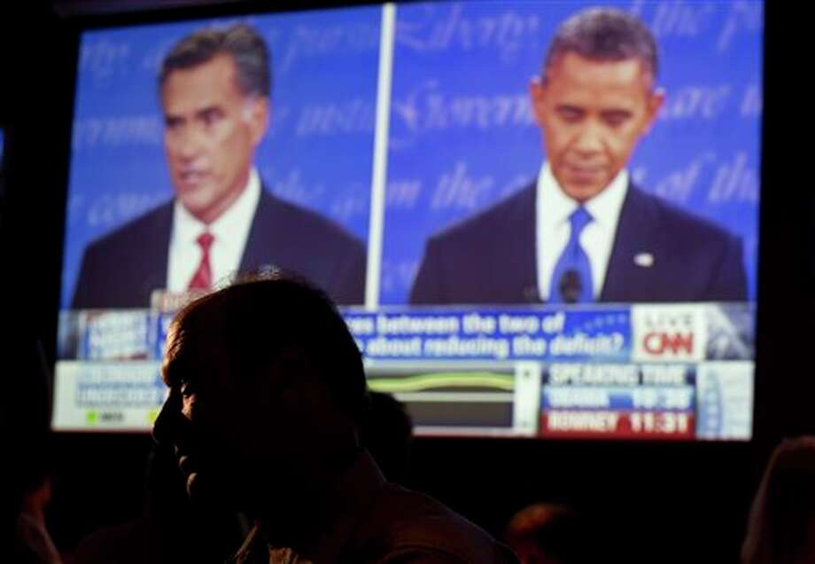 John Rossitto watches the first presidential debate between President Barack Obama and Republican presidential nominee Mitt Romney from a restaurant in San Diego, Wednesday, Oct. 3, 2012. (AP Photo/Gregory Bull) Photo: Gregory Bull / AP
