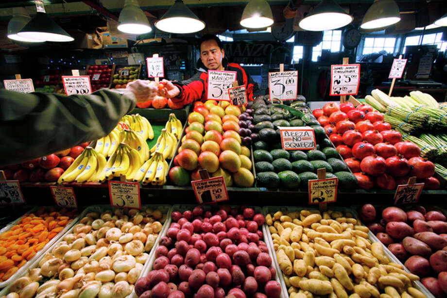 FILE - In this Nov. 12, 2009 file photo, a vendor hands over a sample of produce to a potential customer at the historic Pike Place Market in Seattle. A healthy diet is expensive and could make it difficult for Americans to meet new U.S. nutritional guidelines, according to a study published Thursday, Aug. 3, 2011 that says the government should do more to help consumers eat healthier. (AP Photo/Elaine Thompson, File) Photo: Elaine Thompson / AP2009