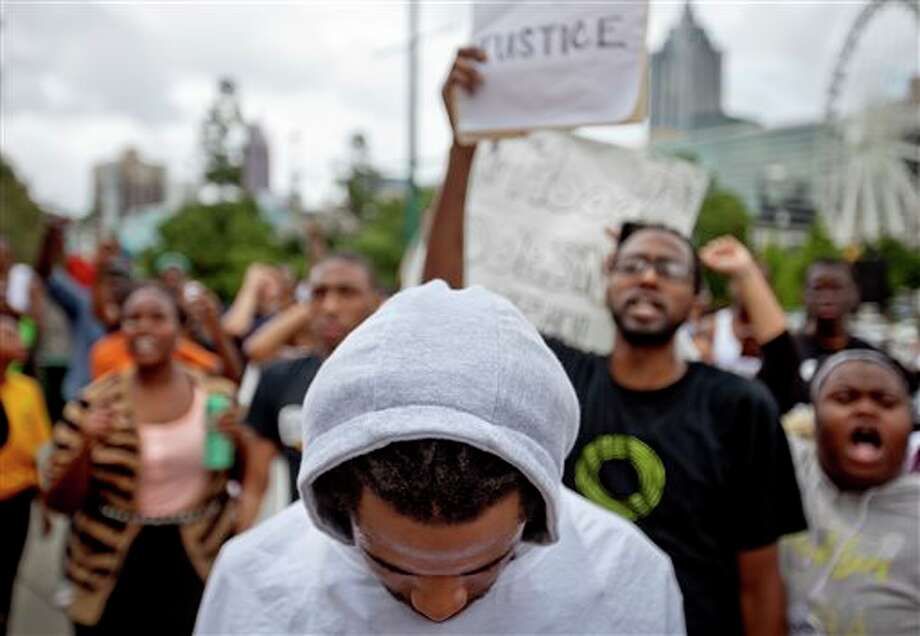 (File Photo) A demonstrator wears a hoodie during a protest the day after George Zimmerman was found not guilty in the 2012 shooting death of teenager Trayvon Martin, Sunday, July 14, 2013, in Atlanta. Photo: David Goldman / AP