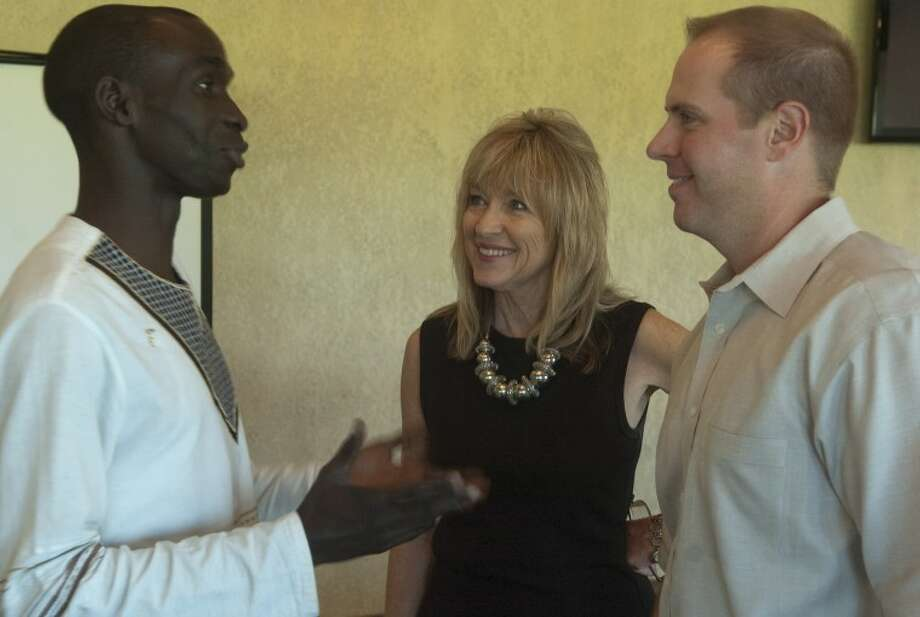 Ronald Ongopa, Habitat Uganda, talks with Alynda Best, Midland director of Habitat and Jacob Hooper, Midland board president, during a luncheon Tuesday at Ranchland Hills Country Club. Photo: Tim Fischer/Reporter-Telegram