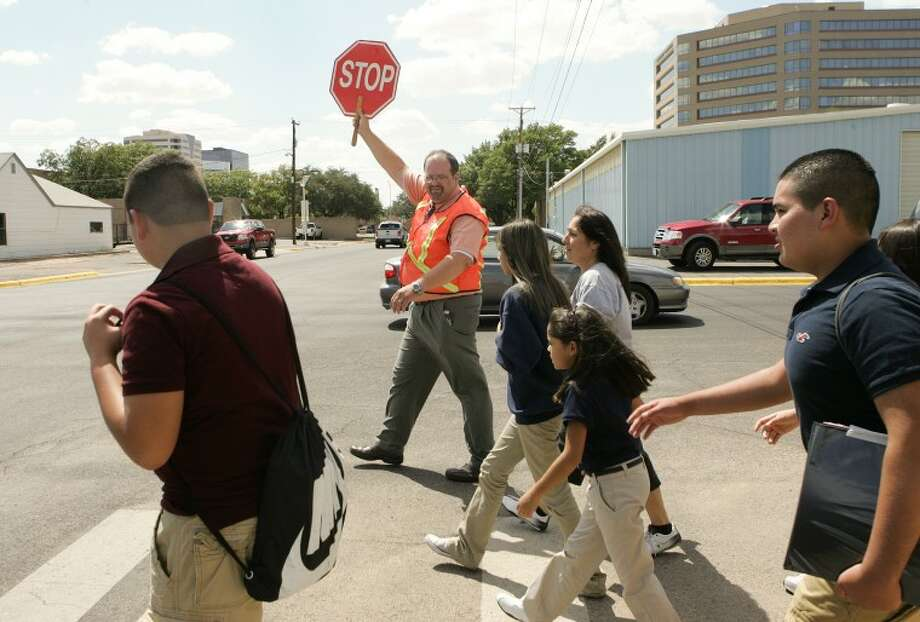 Derek Wooten assists students and their parents with safely crossing the street Monday at Midland Academy Charter School. Cindeka Nealy/Reporter-Telegram Photo: Cindeka Nealy