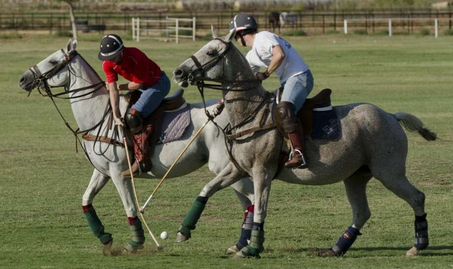 Jared Muncy, left, hits the ball backwards as Joey Hopkins chases during polo school Sept. 17, at the Midland Polo Club. Tim Fischer/Reporter-Telegram Photo: Tim Fischer