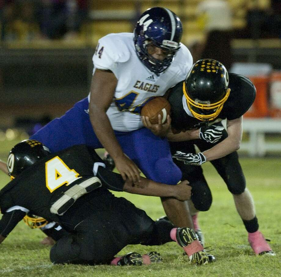 Sterling City's Joseph Block is stopped by Grady's EL Rodriguez, 4, as Brandon Lucas comes in to help bring him down Friday night at M.W. Tunnell Field in Grady. Tim Fischer\Reporter-Telegram Photo: Tim Fischer